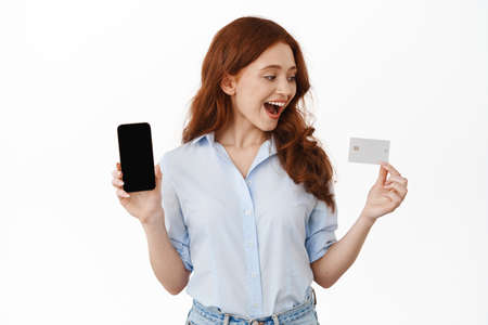 Wondered happy girl with ginger hair, looking fascinated at credit card, showing empty phone screen, application or bank account, white background