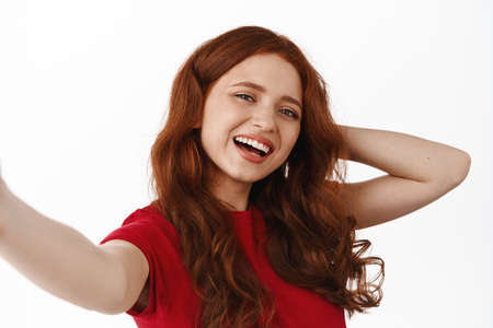 Close up portrait of ginger girl taking selfie on smartphone, posing at camera, laughing and smiling happy, standing in t-shirt against white background