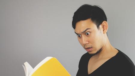 sorprendido: El hombre asiático está conmocionado por un libro amarillo.