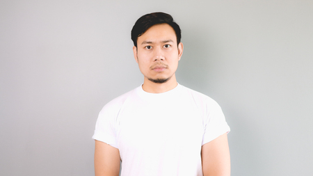 Straight face. An asian man with white t-shirt and grey background.