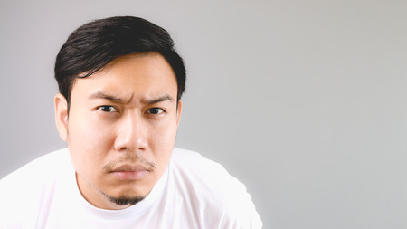 Close up staring at the camera. An asian man with white t-shirt and grey background.