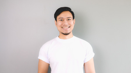 Smile straight face. An asian man with white t-shirt and grey background. 写真素材
