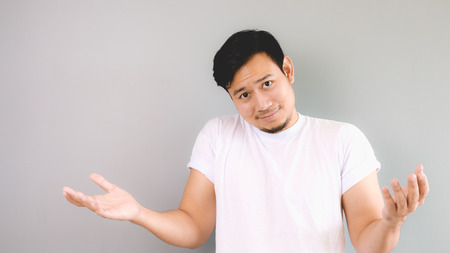 disrespect: Rasing his shoulder and arms as he does not care. An asian man with white t-shirt and grey background.