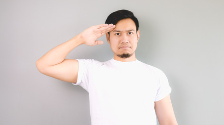 A man in salute pose and serious face. An asian man with white t-shirt and grey background.