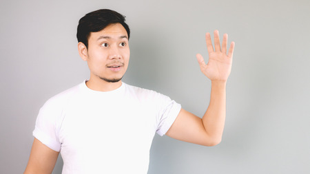 waving: Waving hand to someone as hi or goodbye. An asian man with white t-shirt and grey background.
