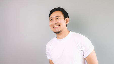 A man looking out and smile. An asian man with white t-shirt and grey background.