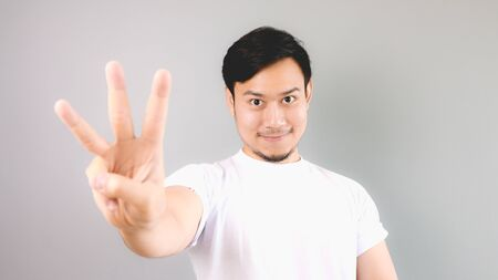 Three hand sign. An asian man with white t-shirt and grey background.