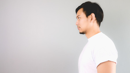 A man look straight to the side. An asian man with white t-shirt and grey background. 写真素材