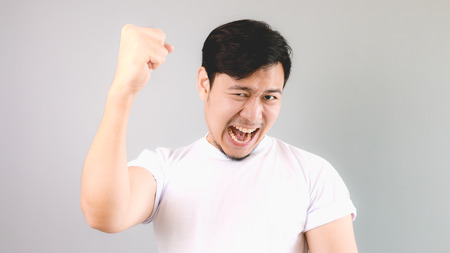 Victorious man. An asian man with white t-shirt and grey background.