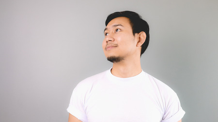 man looking out: A man looking out and smile like day dreaming. An asian man with white t-shirt and grey background. Stock Photo