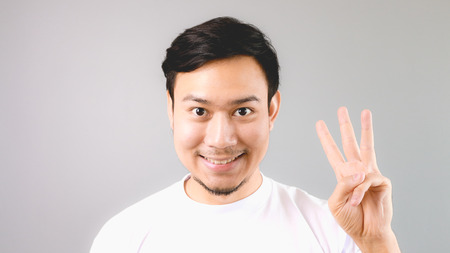 A man showing hand sign the third thing. An asian man with white t-shirt and grey background. Stock Photo