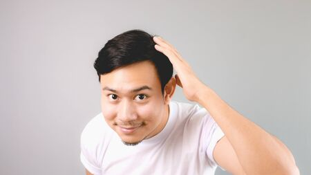 comb hair: Sorry sign and pose of asian. An asian man with white t-shirt and grey background.