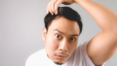 calvicie: Un hombre busca en el espejo y sorprendido de que está perdiendo el pelo. Un hombre asiático con la camiseta blanca y fondo gris.