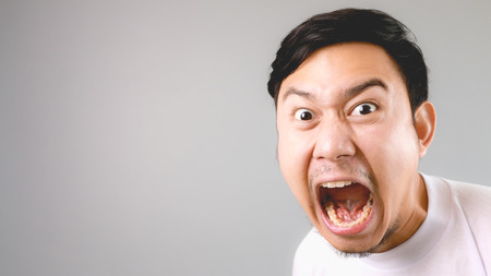 Shouting at the camera. An asian man with white t-shirt and grey background.
