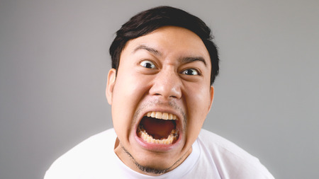 Commanding loudly at the camera. An asian man with white t-shirt and grey background.