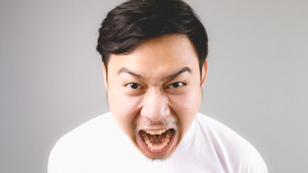 Blaming out loud at the camera. An asian man with white t-shirt and grey background. Stock Photo