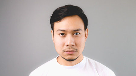 straight man: A sleepy straight face. An asian man with white t-shirt and grey background.
