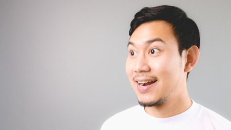 Wow face on empty copyspace. An asian man with white t-shirt and grey background.