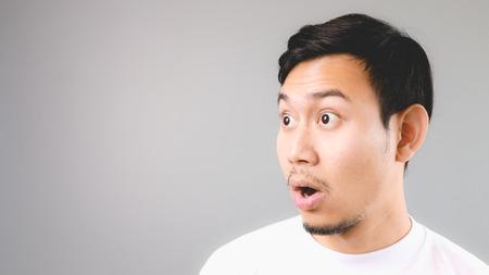wow: Cara Sorpresa en copyspace vacía. Un hombre asiático con la camiseta blanca y un fondo gris. Foto de archivo
