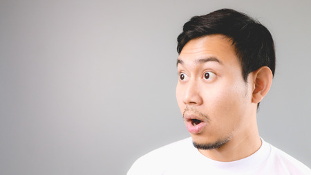 expression: Surprise face on empty copyspace. An asian man with white t-shirt and grey background.