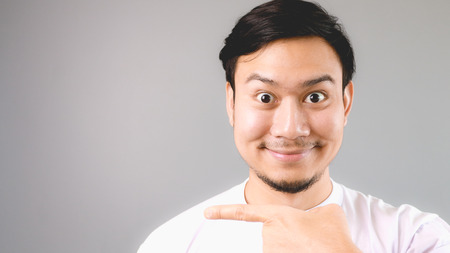 Pointing at the empty copyspace with smile happy face. An asian man with white t-shirt and grey background.