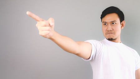 He is blaming or firing someone. An asian man with white t-shirt and grey background. Stok Fotoğraf