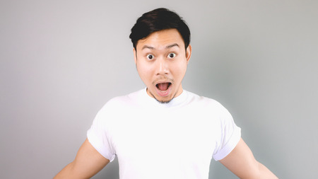 Surprised face and pose. An asian man with white t-shirt and grey background.