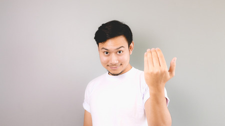 to beckon: Inviting or calling hand sign. An asian man with white t-shirt and grey background.