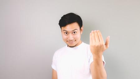 Uitnodigen of te bellen handteken. Een Aziatische man met wit t-shirt en een grijze achtergrond. Stockfoto