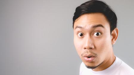 Wow, das ist er überrascht, die Nachrichten zu hören. Ein asiatischer Mann mit weißem T-Shirt und grauen Hintergrund.