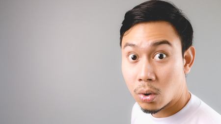 expression: Wow, He is surprised to hear the news. An asian man with white t-shirt and grey background. Stock Photo