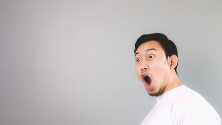 Shock face on empty copyspace. An asian man with white t-shirt and grey background. Standard-Bild