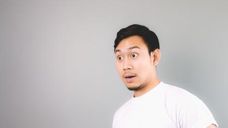 cara sorpresa: Cara Sorpresa en copyspace vac�a. Un hombre asi�tico con la camiseta blanca y un fondo gris. Foto de archivo