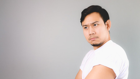 Can not be trust face on empty copyspace. An asian man with white t-shirt and grey background.