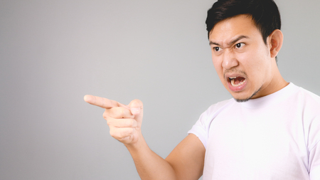 He is blaming someone. An asian man with white t-shirt and grey background.