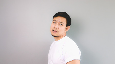 asian youth: Boring face and pose. An asian man with white t-shirt and grey background.