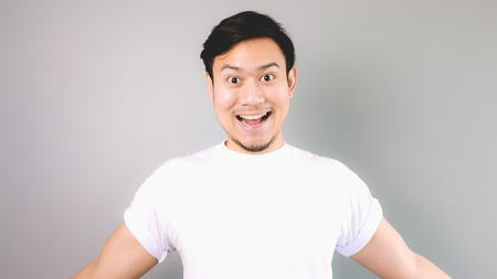 Wow, he is happy and ready to hug you. An asian man with white t-shirt and grey background.
