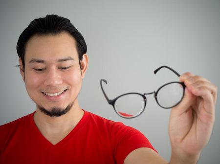 Asian man is taking off the eyeglasses. 写真素材