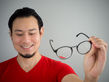 Asian man is taking off the eyeglasses. Stock Photo