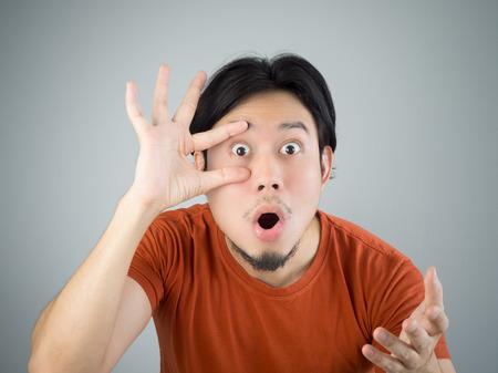 Überrascht asiatischer Mann im roten T-Shirt. Standard-Bild
