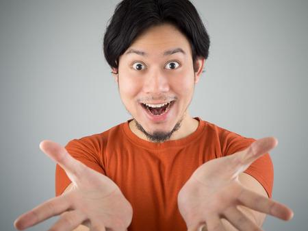 Surprised Asian man showing something.