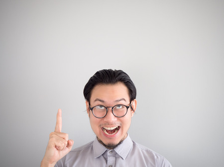 Very happy Asian business man pointing on empty space.