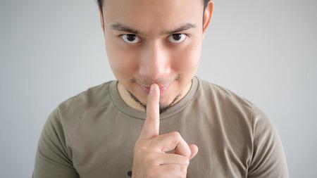 guardar silencio: El hombre asiático está diciendo un secreto. No le digas a nadie.