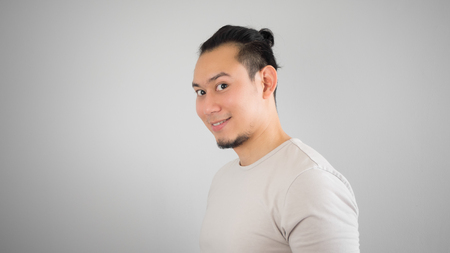Happy Asian hipster man with man bun hair style.