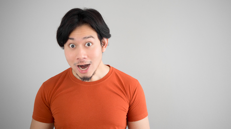 red tshirt: Surprised Asian man in red t-shirt.