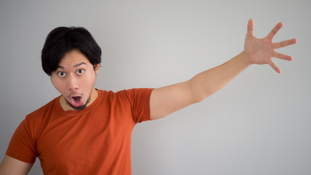 red tshirt: Asian man in red t-shirt get some exciting item. Stock Photo