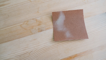 sandpaper: Cleaning stain on wooden table with sandpaper.