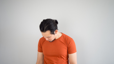 red tshirt: Sad Asian man in red tshirt. Stock Photo