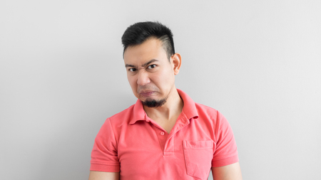vengeance: Asian man in pink shirt feeling hate. Stock Photo