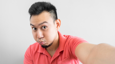 Asian man is taking duck face selfie. 写真素材